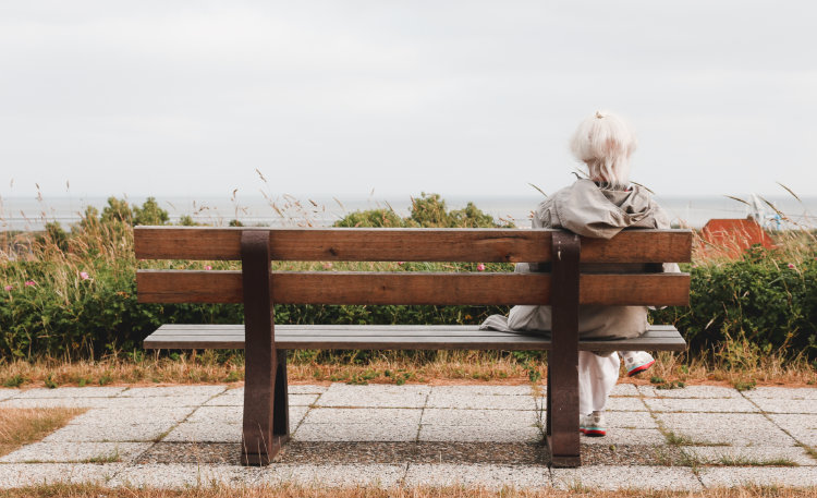 A photo of an elderly lady, sitting on a bench and looking out to sea.