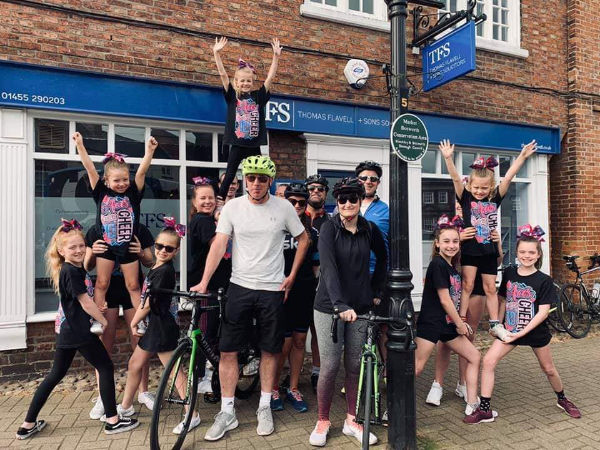 The Thomas Flavell team on bicycles with support from a children's dance troup